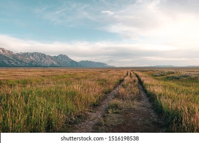 A gravel road through the open prairie grass off the Mormon Row Historical District in Grand Teton National Park, Wyoming, USA.