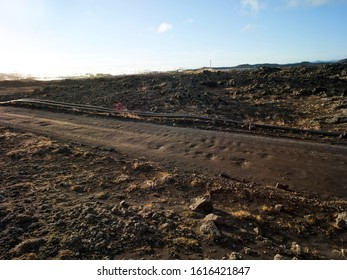 Gravel road in volcanic area in Iceland with pipeline. Backplate for offroad 4x4 4WD cars.