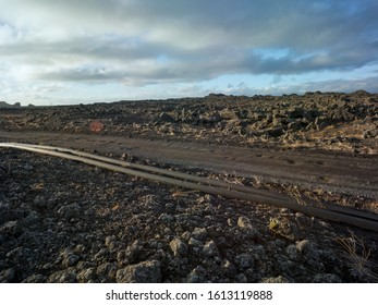 Gravel road in volcanic dramatic area in Iceland with pipeline. Backplate for offroad 4x4 4WD cars from a higher angle.