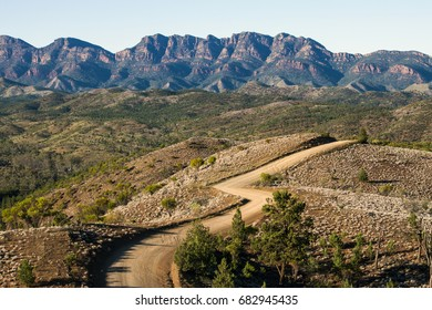 A gravel road weaves across rolling countryside toward the ramparts of Wilpena Pound in South Australia's Flinders Ranges.