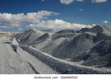 Gravel storage near the quarry for limestone mining. Piles of fine gravel on a background of blue sky with clouds. Mining industry.