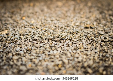 Gravel surface is golden brown. Surface roughness.art