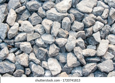 Gravel texture. Pebble stone background. Light grey closeup small rocks. Top view of ground gravel road.