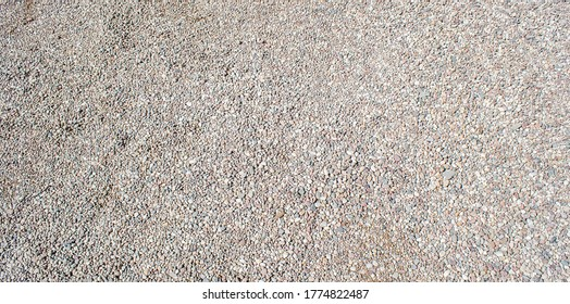 Gravel texture. Small stones, little rocks, pebbles in many shades of grey, white, brown, pink colour. Crushed granite texture. Road made of stones. Small rock background. Banner for web site.