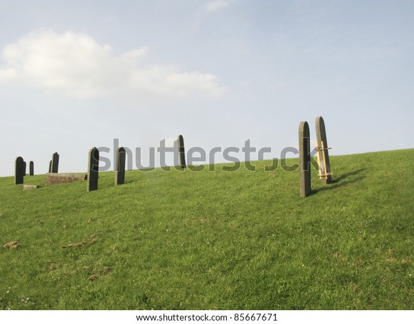 Graves on the dike of the sunken village of Oterdum. Oterdum is a Dutch village wich flooded because of the building of new dikes. The old graves have been restored on the new dike.