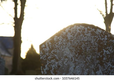 Graves in a very old graveyard in rural England (Church of St Edward, Evenlode) bathed in brilliant golden sunlight during sunset.  Graves are old and the stones are covered with moss and lichen.