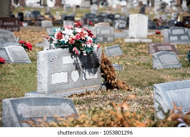 Gravesite headstone in graveyard with flowers and more headstones in background out of focus horizontal