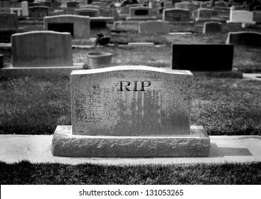 Gravestone in cemetery with words RIP rest in peace carved