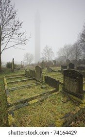 gravestones in misty cemetery with victorian folly in background