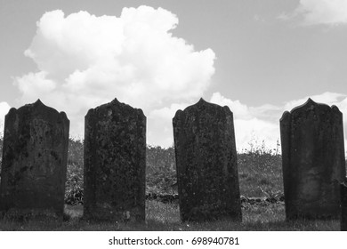 Gravestones silhouetted against the sky at the edge of a churchyard