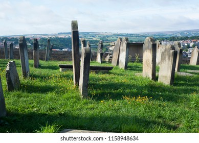Gravestones in a sunny graveyard on top of a hill