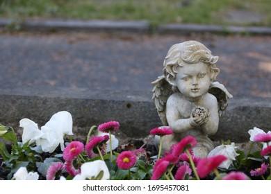 graveyard angel between spring flowers on the roadside
