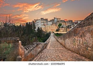 Gravina in Puglia, Bari, Italy: landscape at sunrise of the old town from the ancient aqueduct bridge (viadotto Madonna della Stella) over the deep ravine