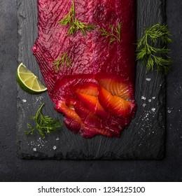 Gravlax,  scandinavian beet cured salmon on black slate board, top view, square image