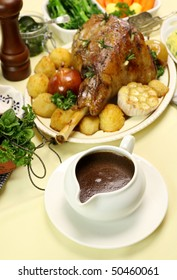 Gravy boat with roasted lamb leg and vegetables.