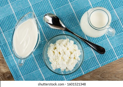 Gravy boat with sour cream, bowl with cottage cheese, metallic spoon, pitcher with milk on blue napkin on wooden table. Top view
