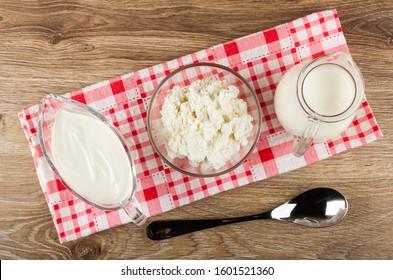 Gravy boat with sour cream, bowl with cottage cheese, pitcher with milk on checkered napkin, spoon on wooden table. Top view