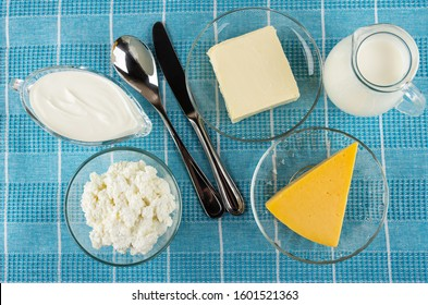 Gravy boat with sour cream, bowl with cottage cheese, metallic spoon, knife, saucers with butter and cheese, pitcher with milk on blue tablecloth. Top view