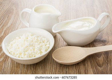 Gravy boat with sour cream, jug milk, cottage cheese and spoon on wooden table