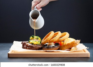 Gravy is poured on a steak with onion rings, mushrooms and potato wedges on a wooden plank