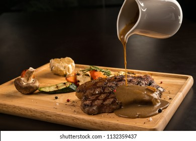 Gravy pouring over grilled seasoned meat, isolated on black