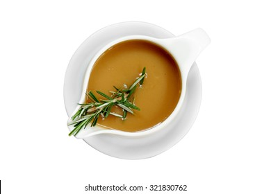 Gravy sauce with rosemary in a gravy boat on white background, isolated