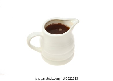 Gravy in a white china jug isolated against white