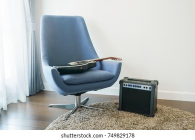 Gray armchair with guitar at corner of living room