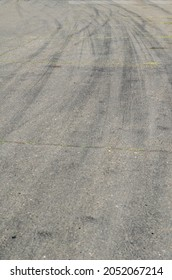 Gray asphalt with black tire tracks. An old country road with cracks. Curved wheel tracks in a bend in the highway.