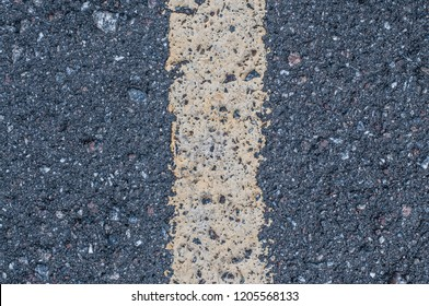Gray asphalt texture. Highway with white solid marking line close up. Cracked road surface, dark background. Transportation track, crevices. Old roadway with stones backdrop. Special marking symbol
