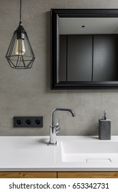 Gray bathroom with black ceiling lamp, mirror in black frame and washbasin