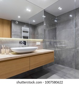 Gray bathroom with long countertop, mirror and walk in shower