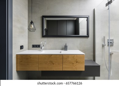 Gray bathroom with modern countertop basin, mirror and shower