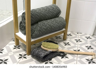 Gray beautifully folded towels on a white shelf with a massage brush and washcloth.