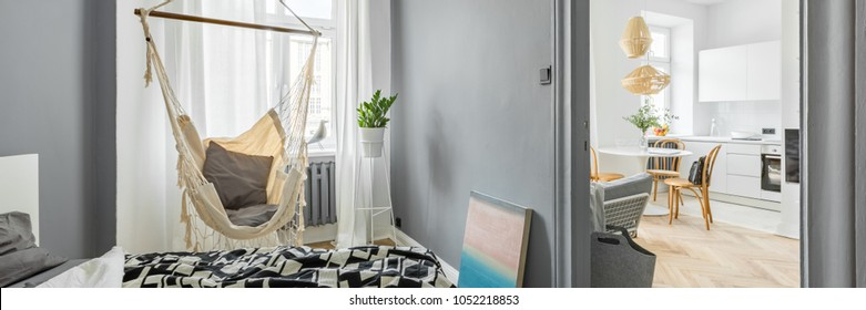Gray bedroom with double bed and hammock, panorama