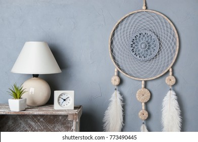 Gray beige dream catcher in bedroom interior on gray textured background. Bedroom decor