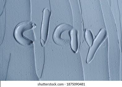 Gray bentonite facial clay (alginate mask, face cream, body wrap) texture close up, selective focus. Word clay on the background.