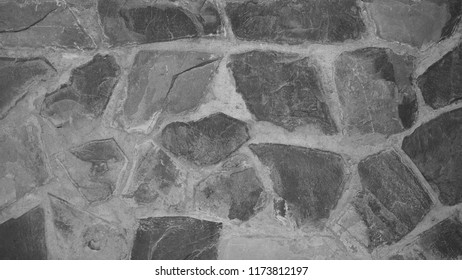 gray black and white old rough stone embed cement on wall and floor