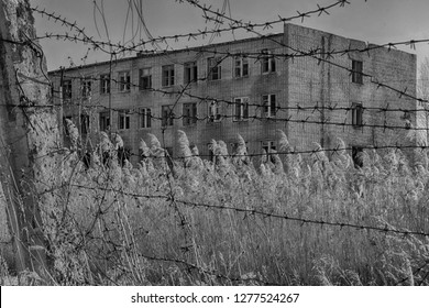 Gray brick building behind barbed wire. Perhaps a prison or military barracks. A sad photo with an atmosphere of pessimism and hopelessness. Monochrome picture