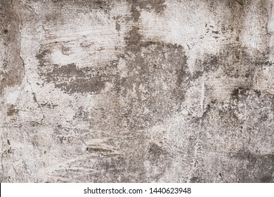 Gray and brown shabby concrete wall with flaky plaster. Torn rough old cement wall texture, background. Vintage, natural cracked distressed background. Empty space, abstract pattern. Grey urban paper