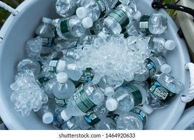 A gray bucket of ice cold Poland spring water June 26, 2019 midget bottles