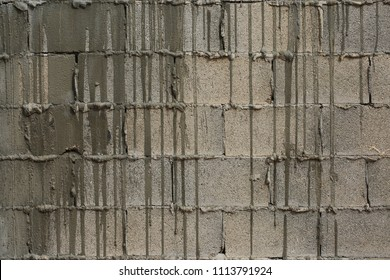 Gray building blocks with leaks of liquid cement