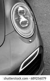 Gray car. Part of the car close-up. Car headlights. Black and white photo