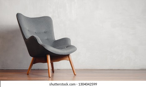 Gray chair in white concrete room for copy space. Concept of minimalism.