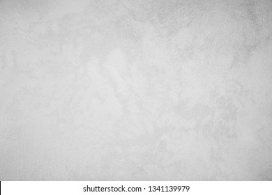 Gray classic texture for the designer background. Rough illuminated surface. Artistically textured background. Concrete wall with plaster. Space to fill. Raster monochrome image.