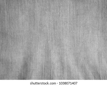 Gray cloth fabric texture background with burlap detail and some dark space.