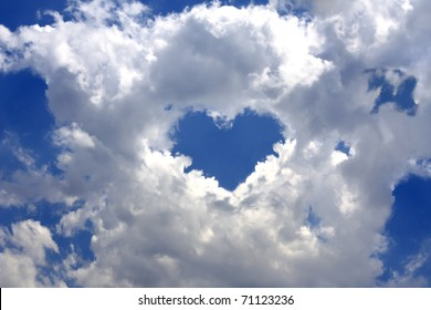 Gray clouds in the blue sky. In the center of the clouds break in the shape of a heart
