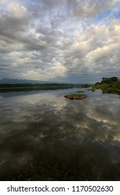 Gray clouds in the sky are reflected in the water of the lake