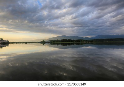 Gray clouds in the sky reflected in the water of the lake at sunset