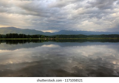 Gray clouds in the sky are reflected in the water of the lake and mountains in the distance